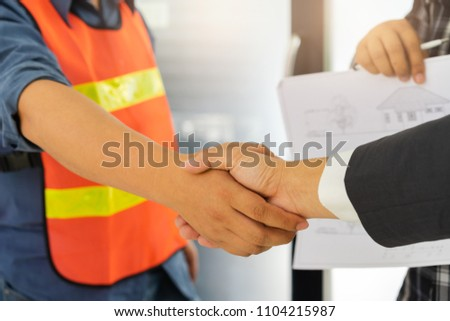 Business people shaking hands after successful building construction planning project and male architect standing holding a blueprint background. #1104215987