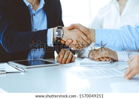Business people shaking hands at meeting or negotiation, close-up. Group of unknown businessmen and women in modern office. Teamwork, partnership and handshake concept, toned picture Foto stock ©