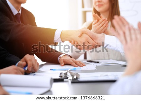 Business people shaking hands at meeting while theirs colleagues clapping and applauding. Group of unknown businessmen and women in modern white office. Success teamwork, partnership and handshake #1376666321
