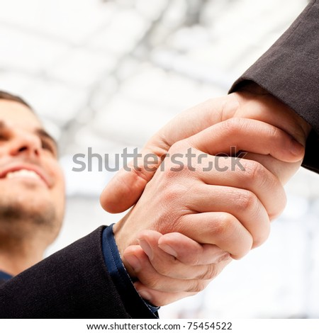 Business people shaking hands. Bright blurred background.