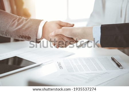 Business people shaking hands finishing contract signing in sunny office, close-up. Handshake and marketing