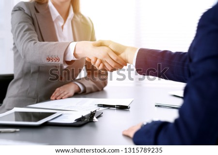Business people shaking hands, finishing up a meeting. Papers signing, agreement and lawyer consulting concept #1315789235