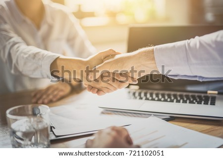 Business people shaking hands, finishing up meeting. Successful businessmen handshaking after good deal.