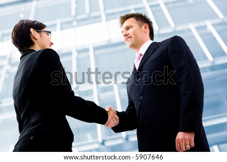 Business people shaking hands in front of an office building. Selective focus is placed on the hands.