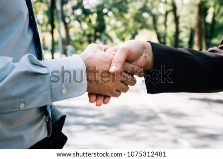 Business people shaking hands in park, finishing up a meeting. A happy business start up welcome, introduction, greet or thanks gesture, partnership approval, dealing, greeting and partner concept. #1075312481