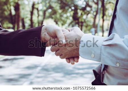 Business people shaking hands in park, finishing up a meeting. A happy business start up welcome, introduction, greet or thanks gesture, partnership approval, dealing, greeting and partner concept. #1075572566