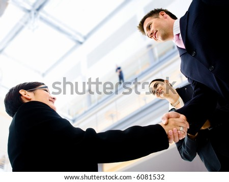 Business people shaking hands in the entrance hall of the office building. Selective focus is placed on the hands.