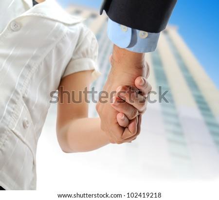 business people shaking hands indoor building background