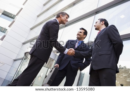 Business people shaking hands outside modern office building