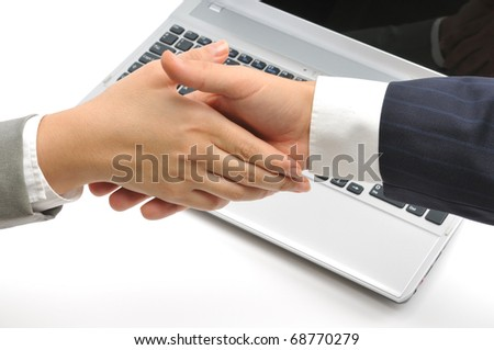 Business people shaking hands over a laptop isolated on white background. - stock photo