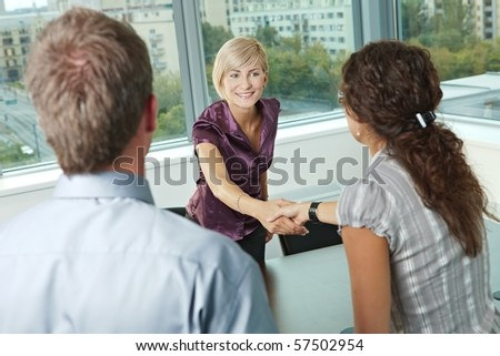 Business people shaking hands over meeting table at office, smiling. - stock photo