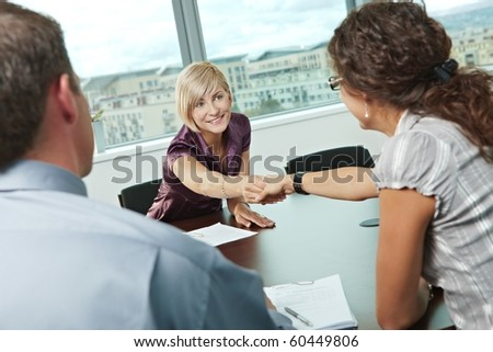 Business people shaking hands over meeting table at office, smiling.