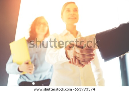 Business people shaking hands. Three women finishing successful meeting. Intentional sun glare