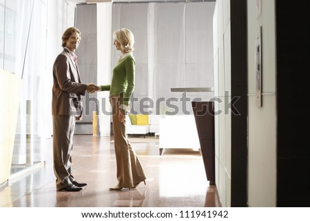 Business people shaking hands while standing at the office lobby - stock photo