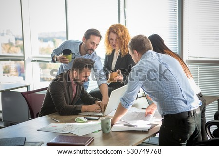 Business people showing team work while working in board room in office interior. People helping one of their colleague to finish new business plan. Business concept. Team work.