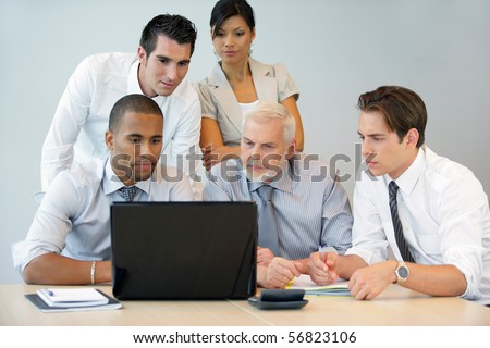 Business people sitting at a desk in front of a laptop computer