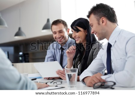 Business people sitting at the desk working with digital tablet
