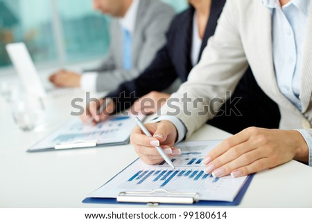 Business people sitting at the table and analyzing graphs