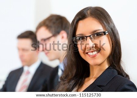 Business people sitting in a meeting or workshop in an office, one woman is looking into the camera