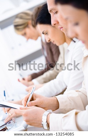 Business people sitting in a row and writing notes. Browse my portfolio for horizontal version.