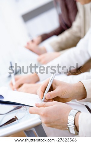 Business people sitting in a row and writing notes. Close-up of writing hands.