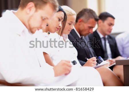 Business people sitting in a row at meeting and making notes. Focus on woman