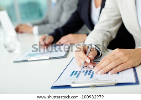 Business people sitting in a row at the meeting, documents lying in front of them on the desk