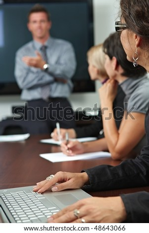 Business people sitting in a row on business training, focus on female hand typing notes on laptop.