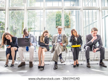 Business people sitting in a waiting room during company\'s bankruptcy - Depressed team of businessmen waiting for a job interview - Concepts about business, bankruptcy, crisis and economic depression