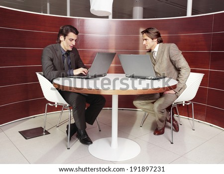 business people sitting in meeting room, working together on laptop computers