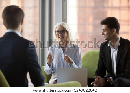 Business people sitting on comfortable couch in contemporary office near panoramic window. Middle aged company ceo and middle eastern ethnicity colleague talking with client discussing working details