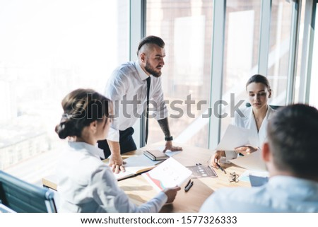 Business people sitting on meeting at table in light office with confident modern executive male standing and strictly asking for results of working process