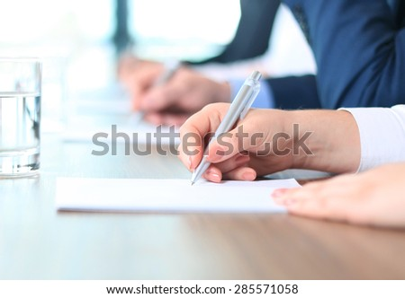 Business people sitting together and making notes at workplace