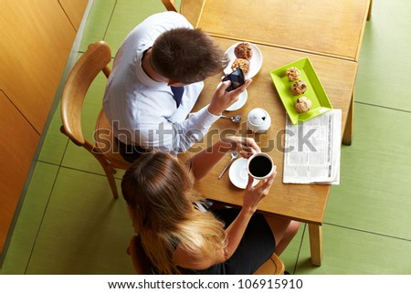 Business people sitting with smartphone in a caf�© for a meeting