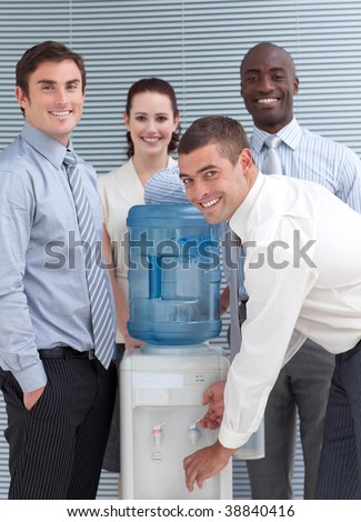 Business people standing around water cooler in workplace