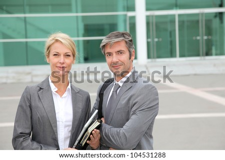 Business people standing in front of exhibition building