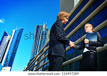 Business people standing in the city and shaking their hands.