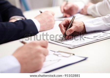 Business people taking notes at briefing