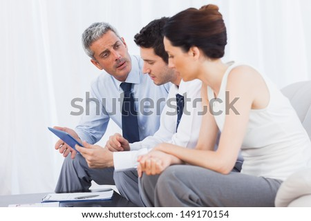 Business people talking about files on sofa at office