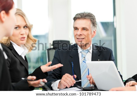 Business people - team meeting in an office, the boss with his employees