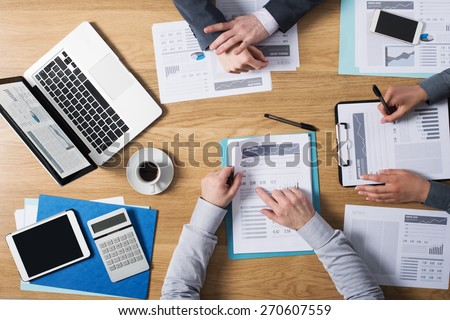 Business people team working together at office desk with laptop, tablet, financial paperwork and reports, top view