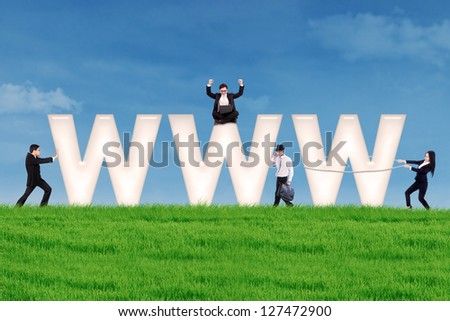Business people using communication tools surround www letter on the green field