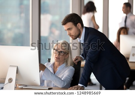 Business people using computer, millennial male employee in formal suit helping explaining to middle aged mature female colleague learn understand corporate program. Mentoring and assistance concept