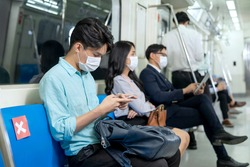 Business people using mobile phone and keep social distancing in subway. Employee wear medical hygiene face mask to prevent the outbreak of coronavirus covid-19 in sky train. New normal life concept.