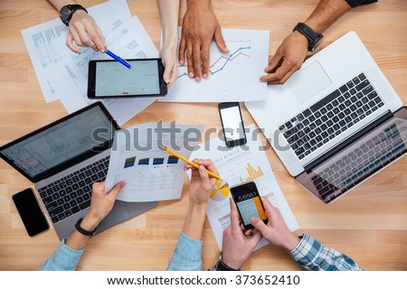 Business people using mobile phones and laptops, calculating and discussing charts and diagrams for financial report