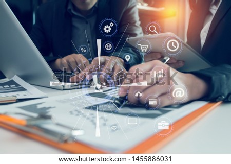 Business people using smartphone and laptop meeting to discuss the situation on the market, Group of colleagues working with startup project in modern office, Graph interfaces icons.  #1455886031