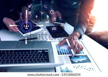 Business people using smartphone and laptop meeting to discuss the situation on the market, Group of colleagues working with startup project in modern office, Graph interfaces icons.  #1455886034