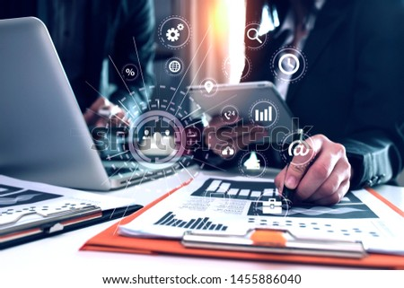 Business people using smartphone and laptop meeting to discuss the situation on the market, Group of colleagues working with startup project in modern office, Graph interfaces icons.  #1455886040