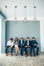 Business people waiting for job interview holding phones and notepad
