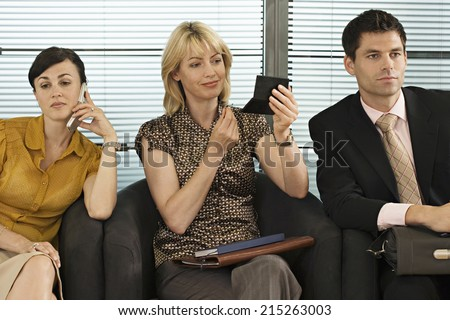 Business people waiting in office reception, woman using mobile phone, second woman applying make-up